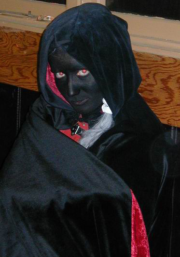 drow watches suspiciously in black and red cloak